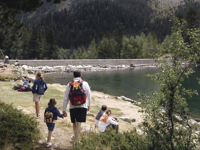 Familia haciendo senderismo al lado de un lago del Parque Nacional d'Aigüestortes, Pallars Sobirà (Jordi Pou)