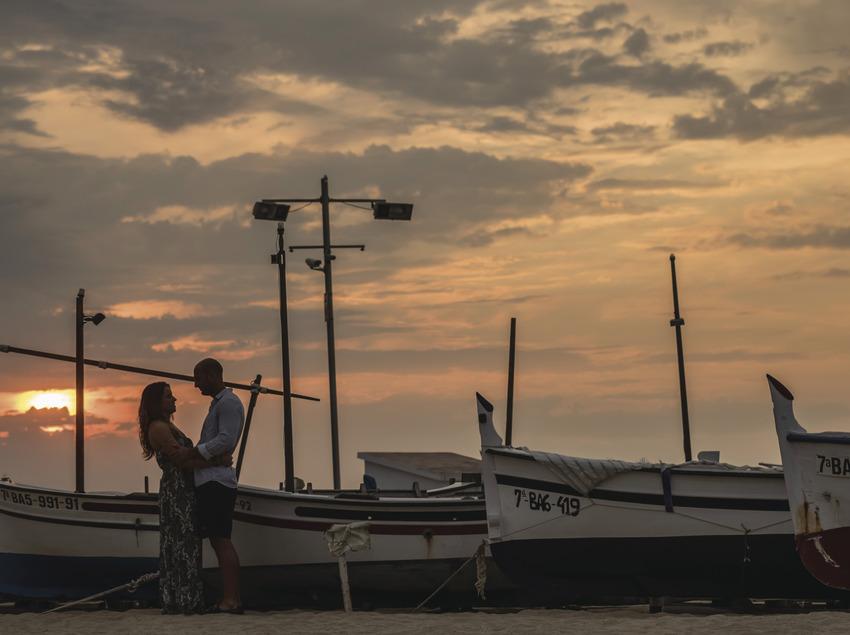 Pareja en la playa de Calonge al lado de unas barcas de pescadores (Ajuntament de Calonge)
