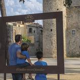Padre con sus hijos haciéndose una fotografía con el Castillo de Calonge de fondo (Ajuntament de Calonge)