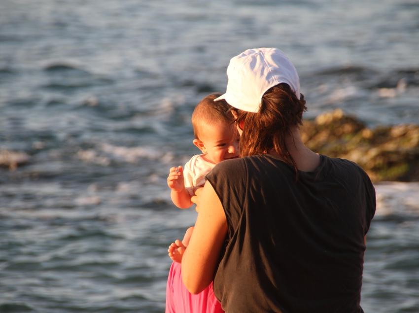 Madre con su bebé delante de la playa de Calella (Ajuntament de Calella)