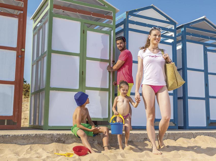 Família davant d'unes casetes de platja a Sant Feliu de Guíxols (Ajuntament de Sant Feliu de Guíxols)
