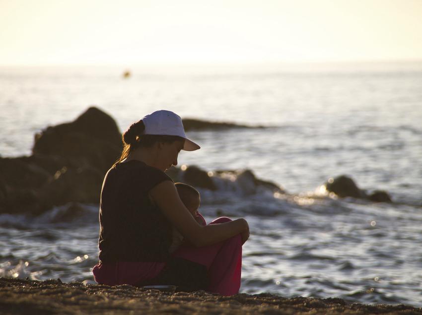 Mare i filla a la platja mirant com surt el sol a Calella (Jaume Bago)