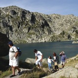 Grup d'excursionistes pujant per un camí a la vora d'un llac al Parc Nacional d'Aigüestortes, Pallars Sobirà (Jordi Pou)