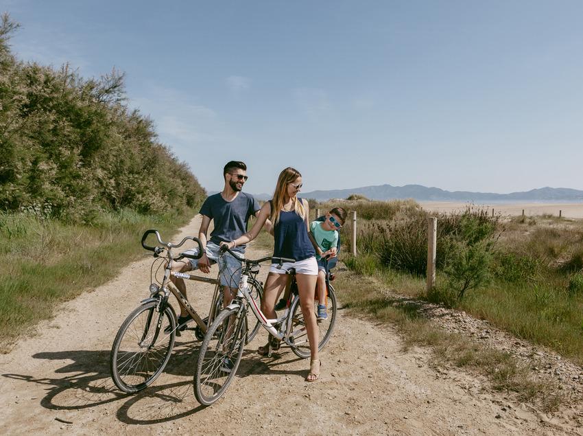 Familia amb bicicleta por una camino al lado de la playa de Sant Pere Pescador (Ajuntament de Sant Pere Pescador)