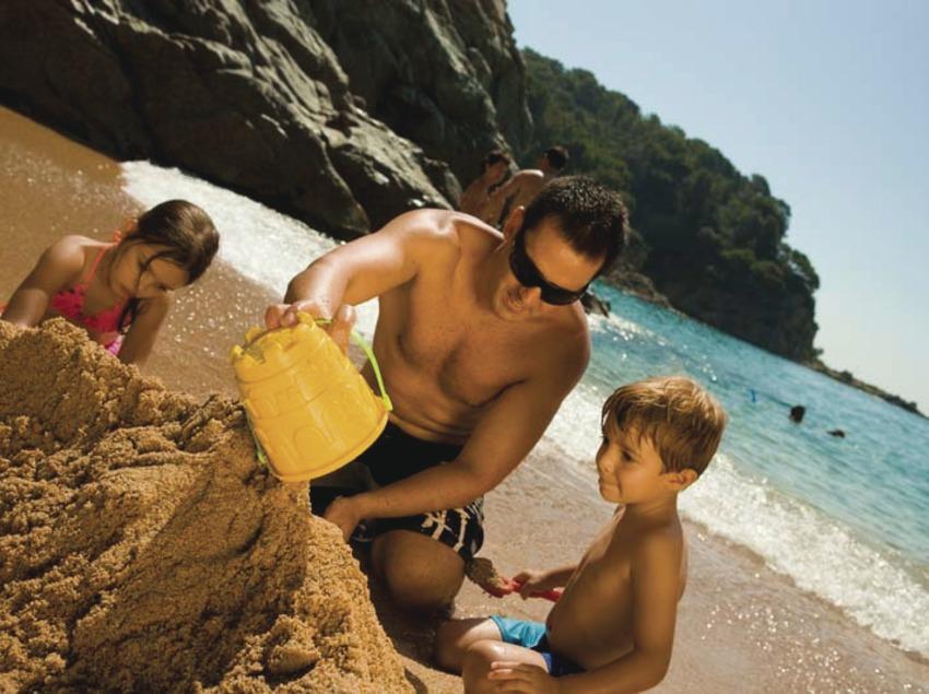 Padre e hijos jugando en la arena de la playa de Lloret de Mar