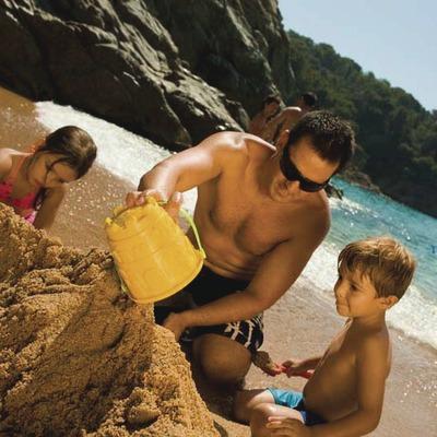 Pare i fills jugant amb la sorra de la platja de Lloret de Mar