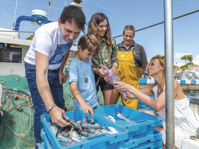 Família en una barca de pescadors a Sant Feliu de Guíxols (Ajuntament de Sant Feliu de Guíxols)