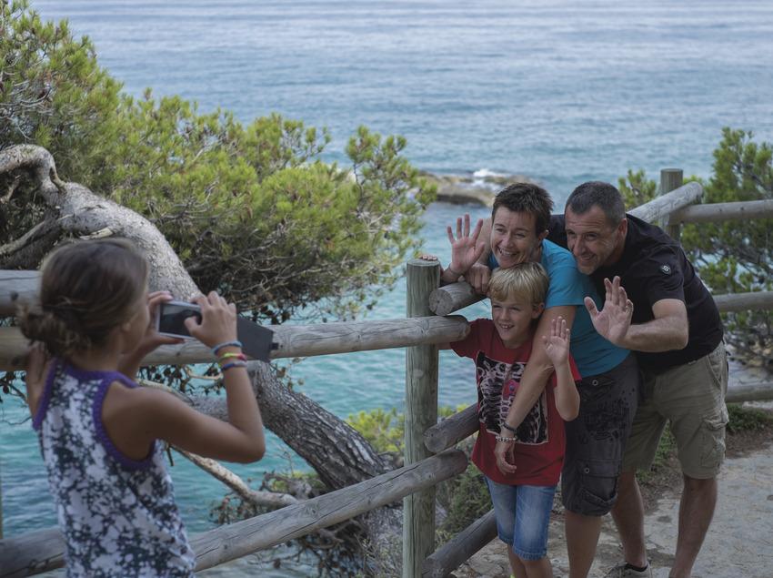 Família fent-se una fotografia en els camins de ronda de Calonge amb el mar de fons (Ajuntament de Calonge)
