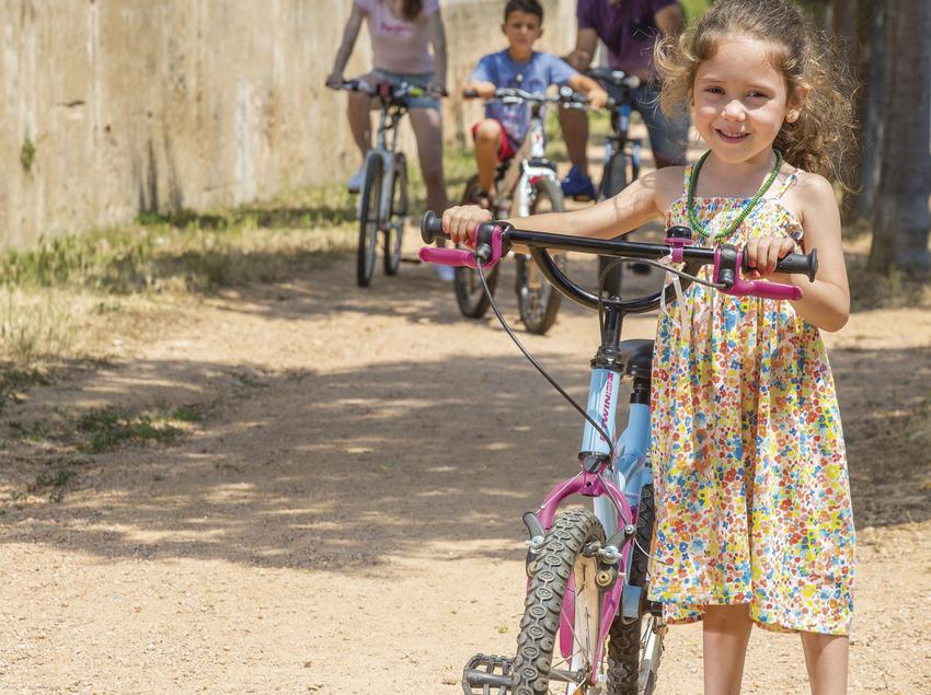 Família amb bicicleta per un camí de terra de Sant Feliu de Guíxols (Ajuntament de Sant Feliu de Guíxols)