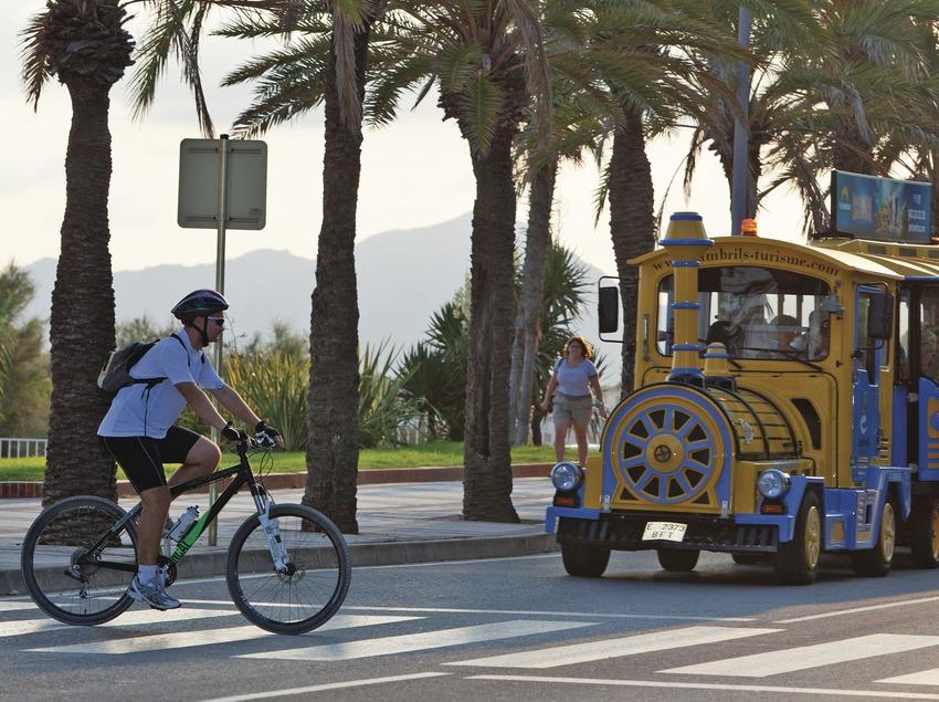 Ciclista creuant el carrer davant del tren turístic de Cambrils (Ajuntament de Cambrils)
