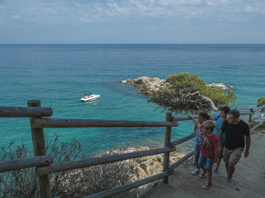 Familia caminando por los Caminos de Ronda con el mar de fondo (Ajuntament de Calonge)