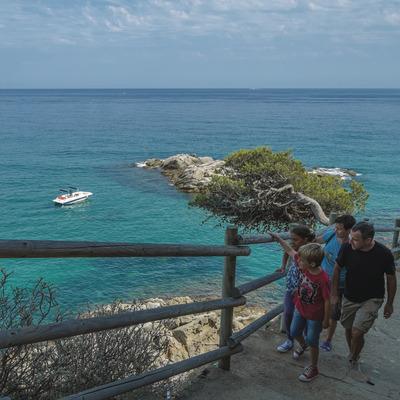 Família caminant pels Camins de Ronda amb el mar de fons (Ajuntament de Calonge)