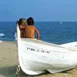 Niña y niño sentados encima de una barca de pescadores en la playa de Calella (Ajuntament de Calella)