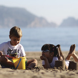Nena i nen jugant a la sorra de la platja de Torroella de Montgrí (Toni Leon)