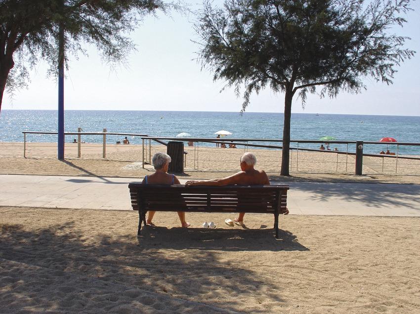 Dues persones segudes en un banc de fusta al passeig de mar de Malgrat de Mar (Ajuntament de Malgrat de Mar)