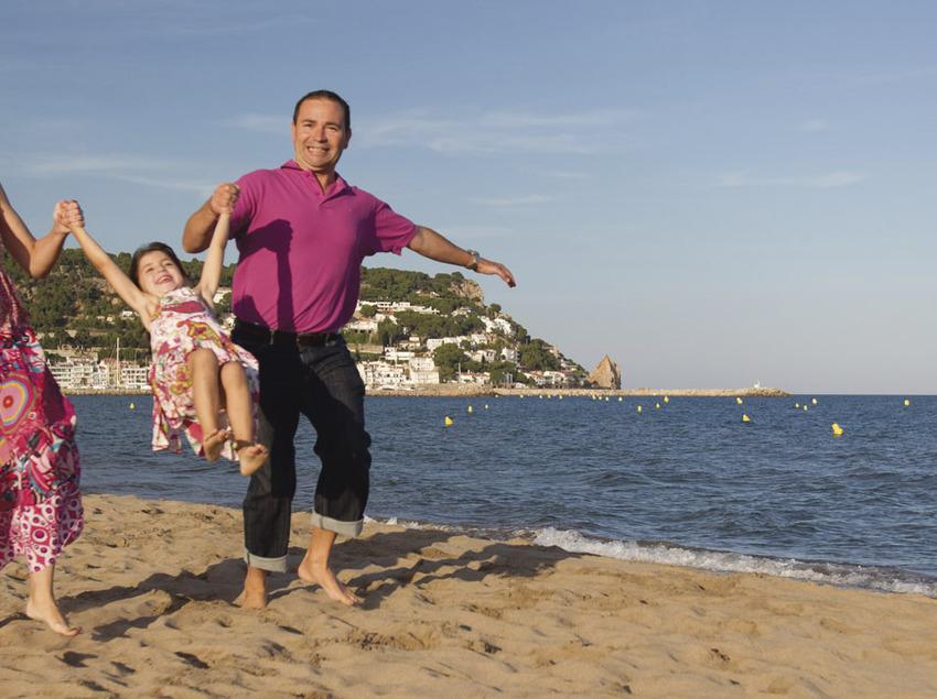 Mare i pare jugant amb la seva filla a la platja de Torroella de Montgrí (Toni Leon)