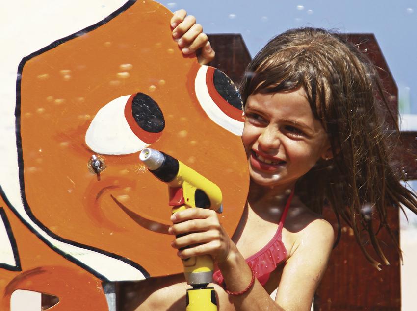 Nena jugant a la platja amb una mànega amagant-se darrere un peix (Ajuntament de Calella)