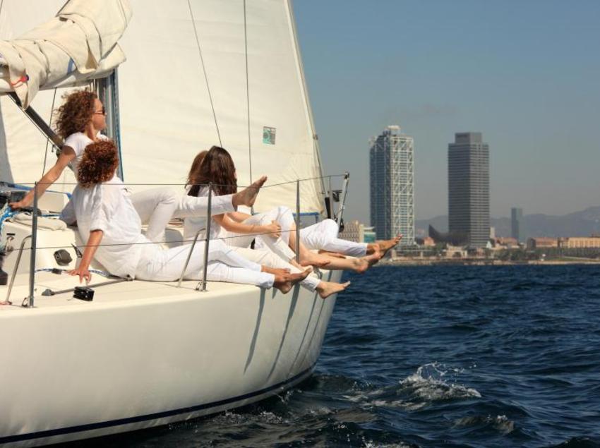 Mujeres vestidas de blanco en una embarcación de vela en la costa de Barcelona.