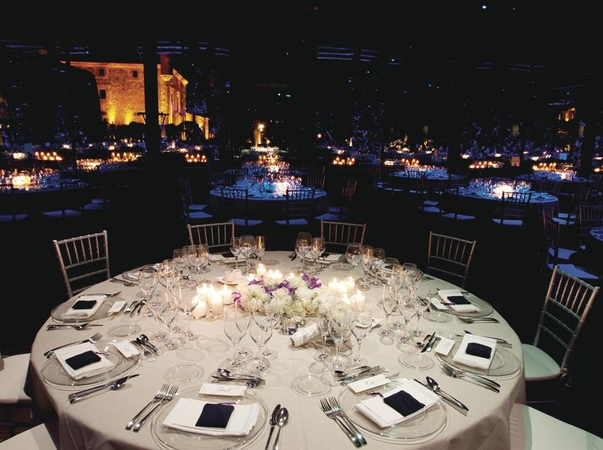 Mesa en el exterior por la noche con Mas Cabañas iluminado al fondo.