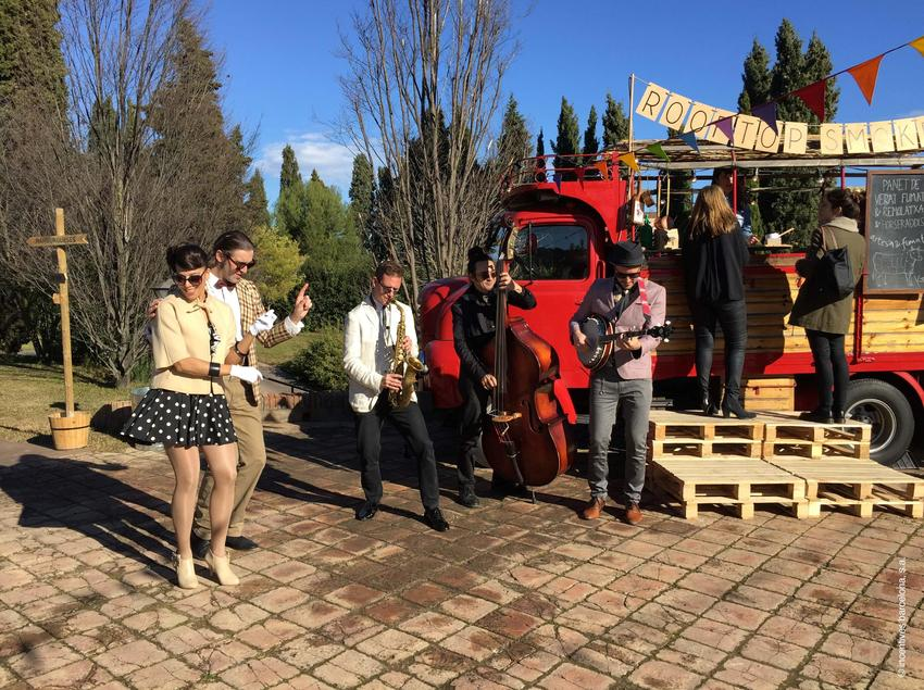 Grup musical tocant davant d'una parada de menjar.