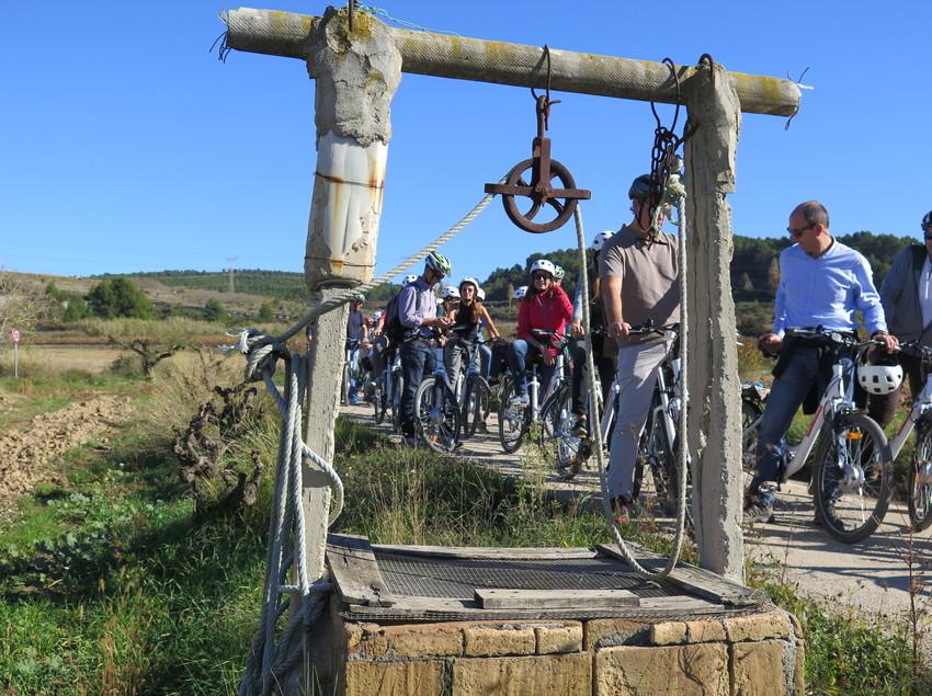 Grupo haciendo cicloturismo detrás del pozo en primer plano. (Bikemotions)