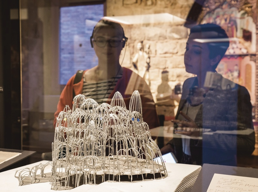 Dos personas contemplando la maqueta de una estructura constructiva de Gaudí. (The Gaudí Exhibition Center)