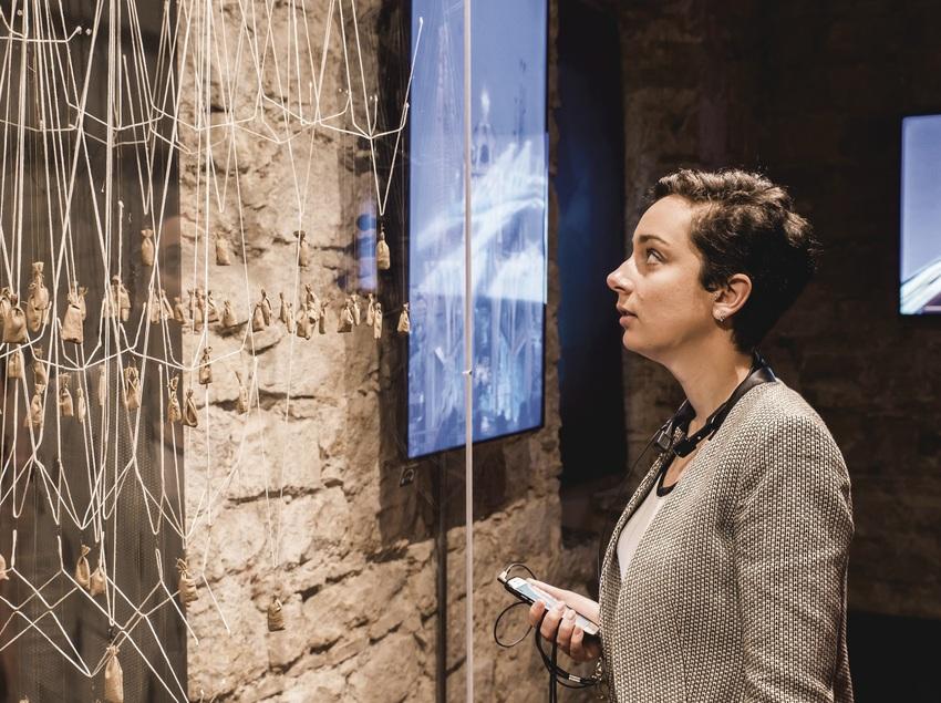 Dona contemplant el sistema de cordes lligades a uns pesos emprat per Gaudí. (The Gaudí Exhibition Center)