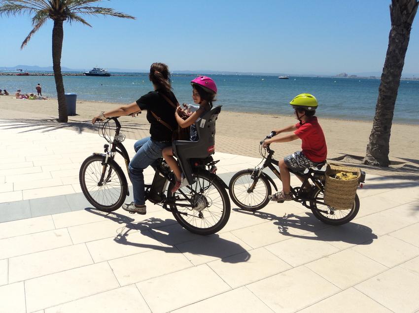 Madre e hijos paseando en Burricleta por un paseo delante del mar (Burricleta Alt Empordà)