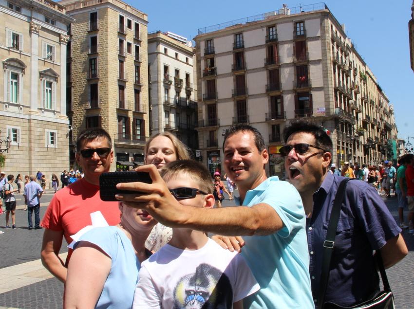 Joves fent-se fotos a la plaça de Sant Jaume.  (Language Tours SL)
