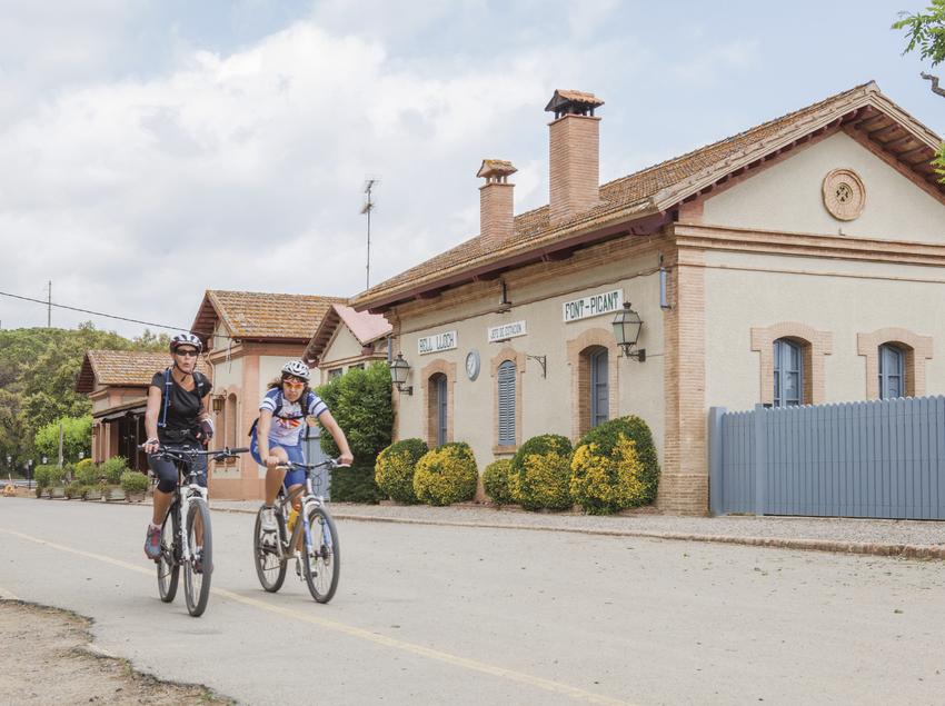 Ciclistes passant vora l'estació de Santa Cristina d'Aro.