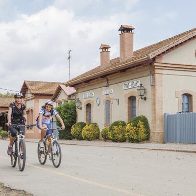 Ciclistas pasando cera de la estación de Santa Cristina d'Aro.