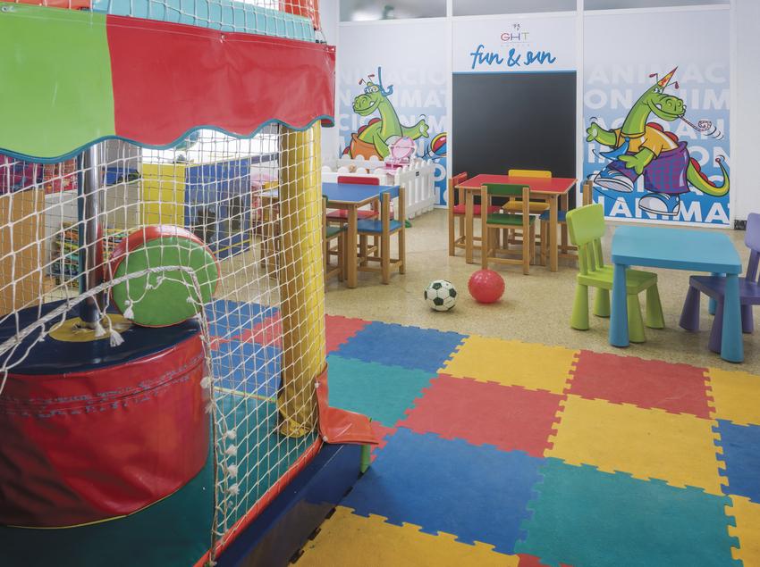 Zona infantil con mesas y sillas.