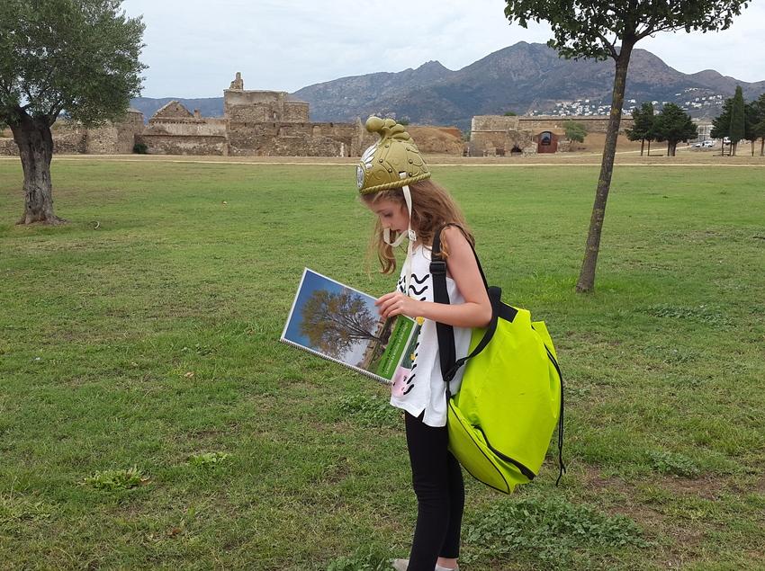 Nena estudiant la vegetació prop d'unes ruïnes.