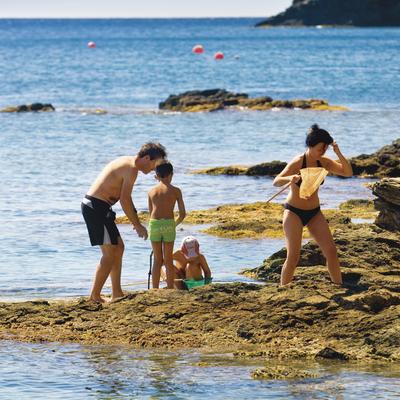 Família jugant a una platja de Roses.