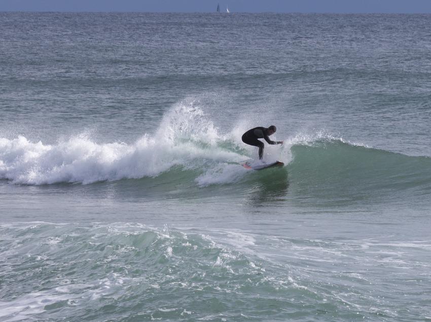 Chico haciendo surf en la playa de Badalona