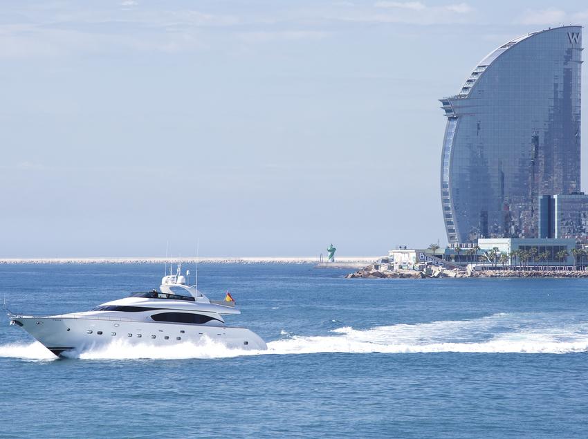 Barco navegando por delante de la costa de Barcelona