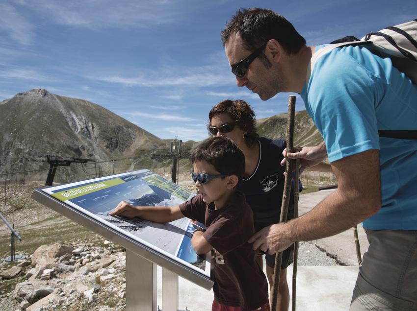 Familia observando el mapa de Vallter 2000 en verano
