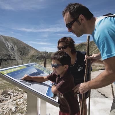 Família observant el mapa de Vallter 2000 a l'estiu
