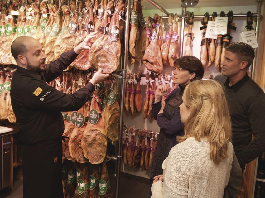 Tour gastronòmic fent parada en una botiga de pernils