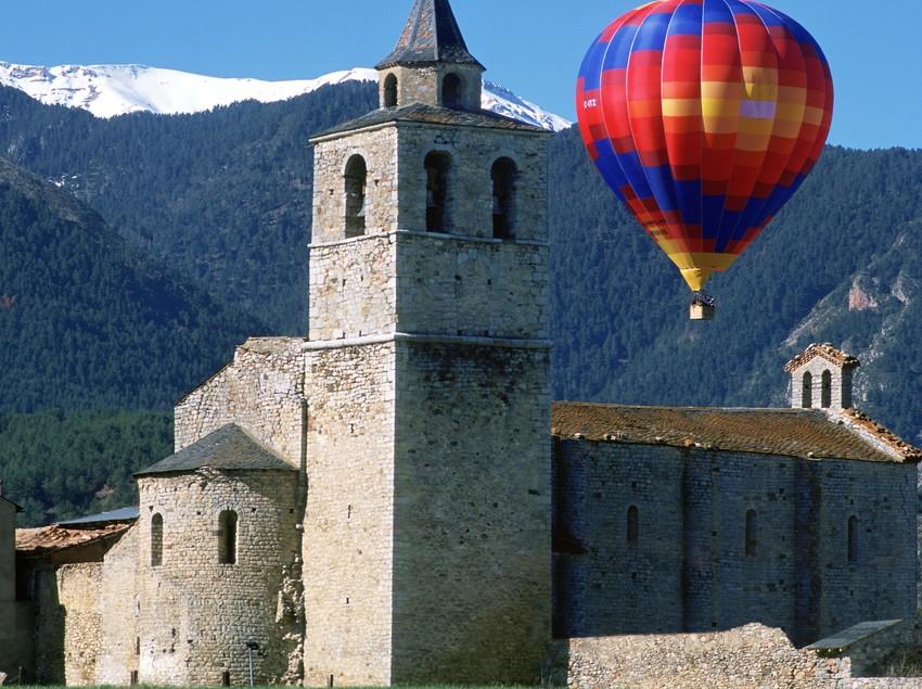 Inglesia de Santa Maria de Talló con un globo aerostàtico en el fondo