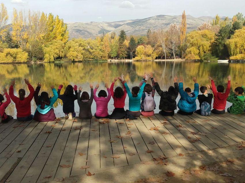 Grupo de escolares sentados frente al lago