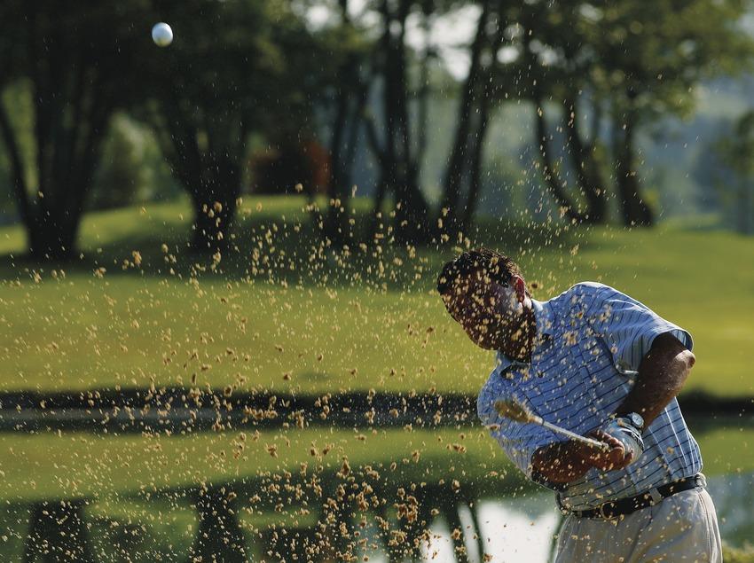 Golfista sacando una bola del búnker.