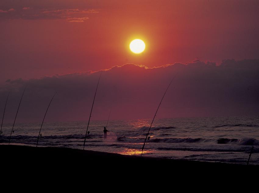Pescadors a una platja del Parc Natural del Delta de l'Ebre al capvespre