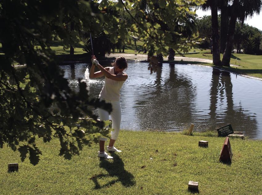 Femme jouant au golf au club de golf Llavaneras