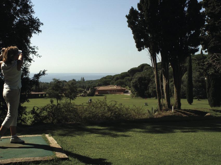 Femme exécutant un swing au club de golf Llavaneras