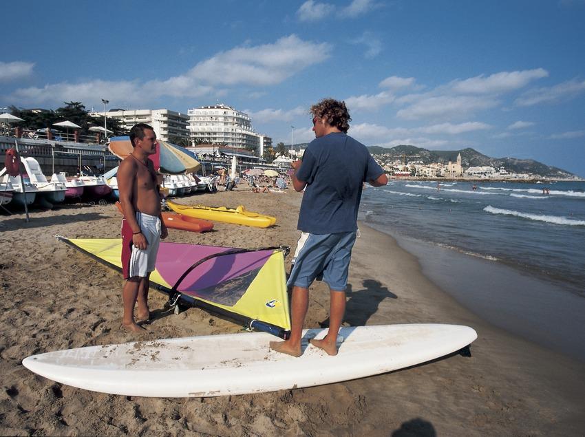 Practicantes de windsurf preparando la vela en la playa.