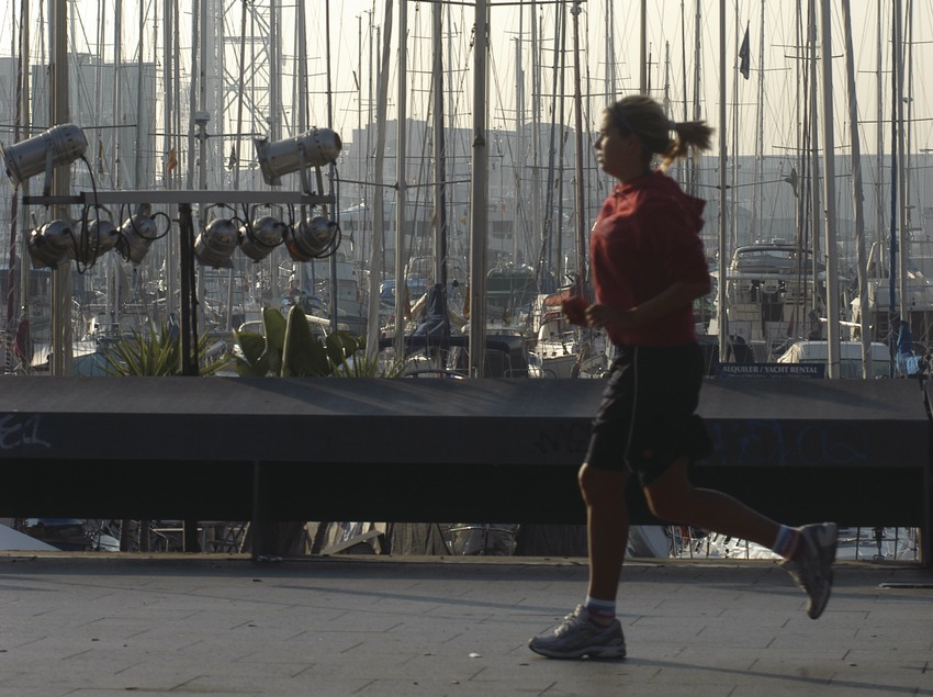 Young woman jogging in front of the Port Vell (old port) in Barcelona