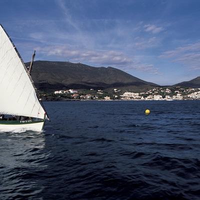 Embarcació de vela llatina navegant davant de Cadaqués