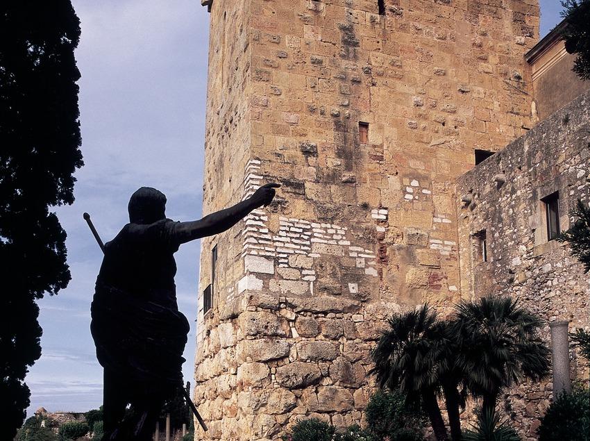 Muralla romana, torre y estatua en el paseo arqueológico.