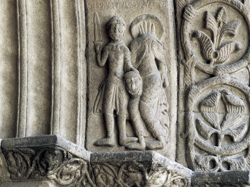 El verdugo presenta la cabeza de San Pablo (siglo XII). Detalle de la portalada de la iglesia del monasterio de Santa Maria de Ripoll.  (Imagen M.A.S.)